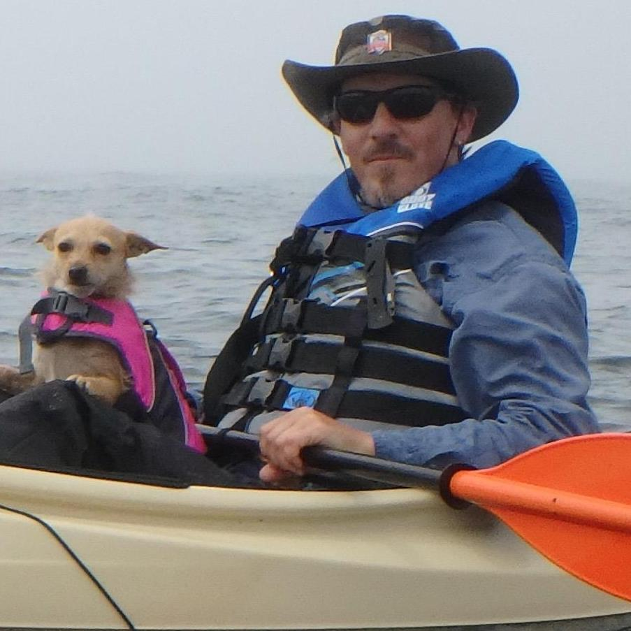 This is what Mike looks like when he is in is in a small boat with a small dog.